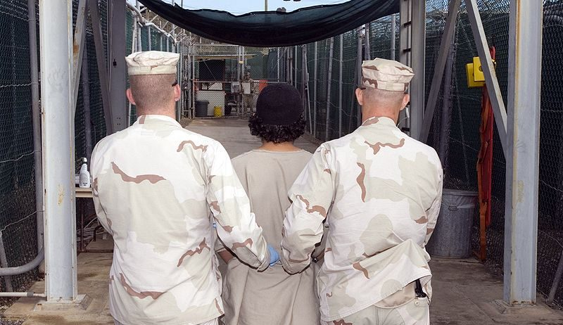 https://history.ubc.ca/wp-content/uploads/sites/23/2021/07/HIST-105B-800px-Captive_being_escorted_for_medical_care_December_2007-Wikimedia-e1626324130229.jpg
